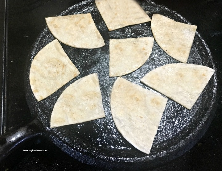 Tortillas on a comal for green enchilada casserole