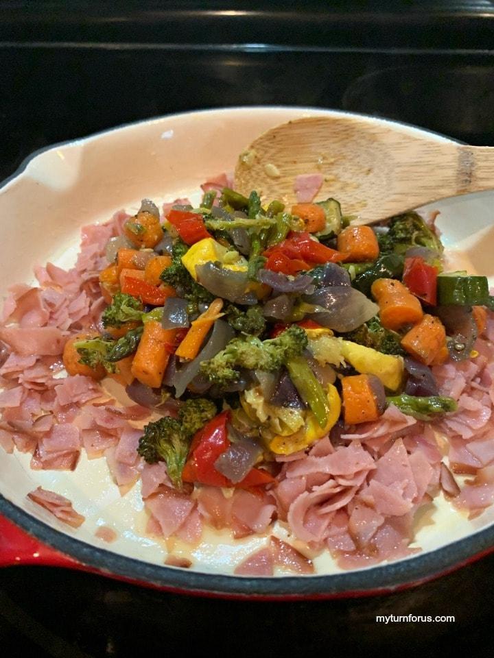 adding leftover veggies in skillet