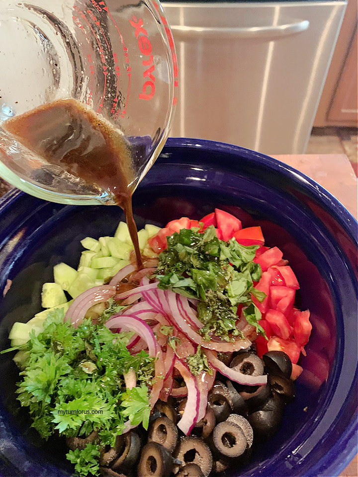 adding dressing to tomato, cucumber and olive salad