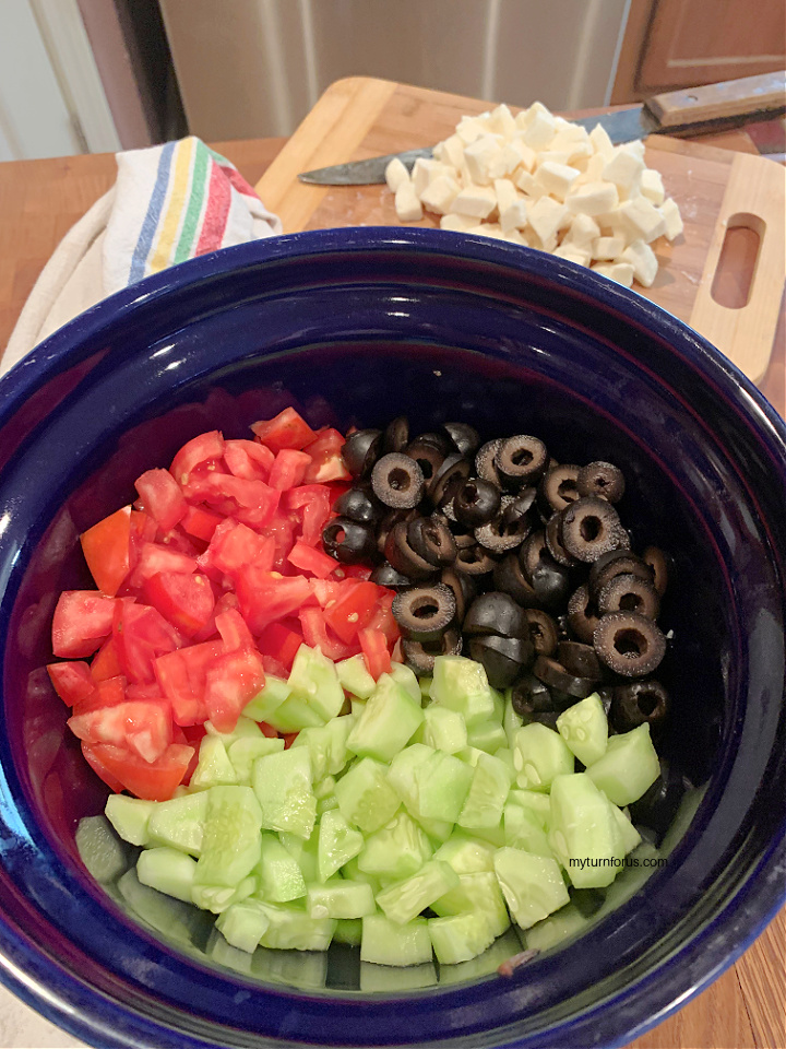 cucumbers, tomatoes and olives in a blue bowl