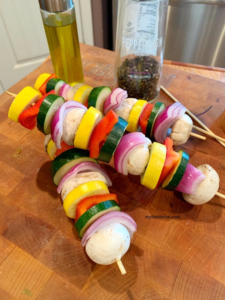 Raw veggie skewers, Squash, zucchini, red bell pepper, purple onion and mushrooms on wooden skewers