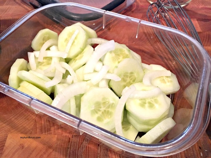 cucumber salad with vinegar, cucumbers with vinegar, sliced cucumbers and onions in a fridge safe dish