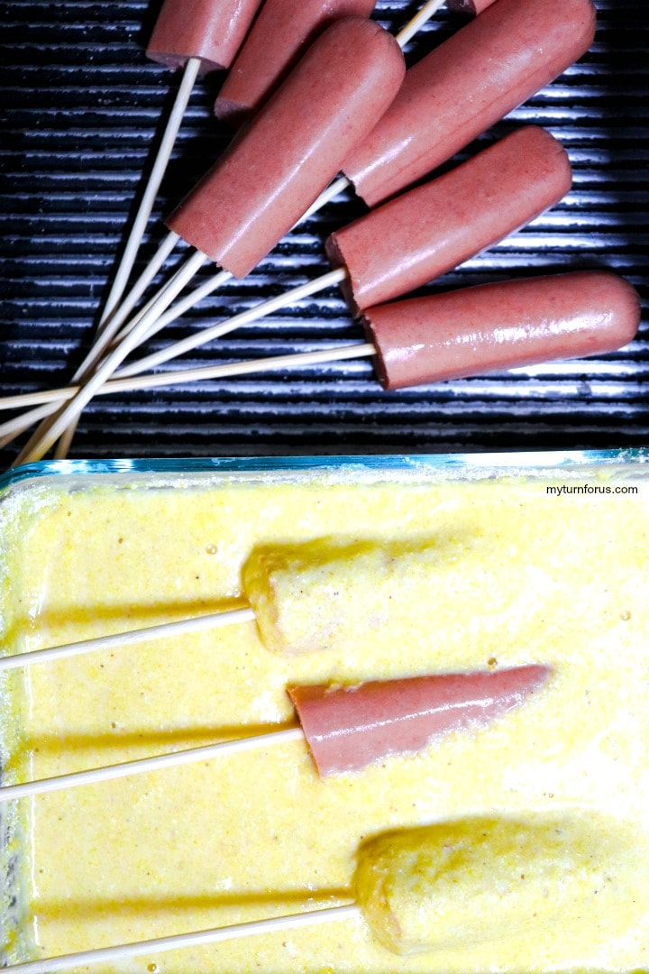 dipping hot dogs into the batter mix