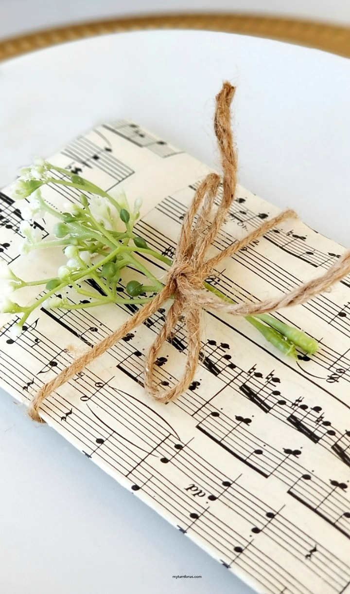 Music paper cutlery pouches tied with jute and with added greenery