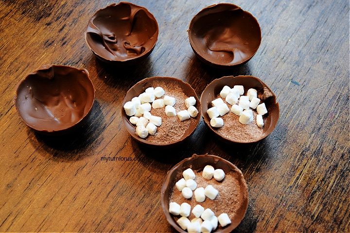 filling hot chocolate bomb shells with marshmallows and hot cocoa mix