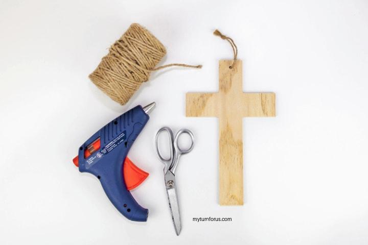 hot glue gun, jute, wooden cross and scissors