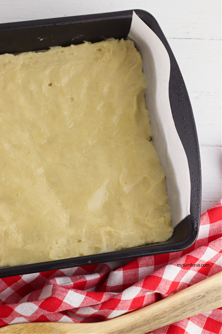 spreading dough layer in pan for apple pie bars